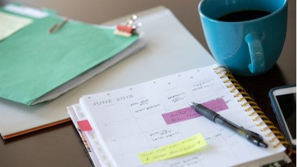 day planner, folder and a cup of coffee sitting on a desk