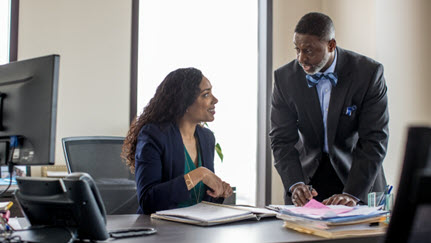 man and woman talking in an office