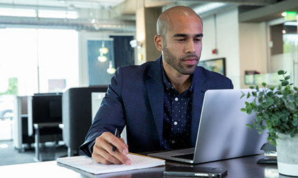 man sitting at a table looking at a laptop