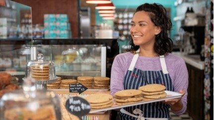 woman holding a tray of cookies at a bakery