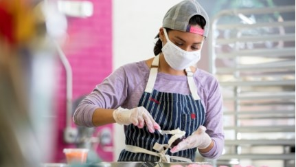 woman wearing a mask and an apron working in a bakery