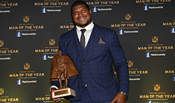 Calais Campbell holding Walter Payton Man of the Year trophy