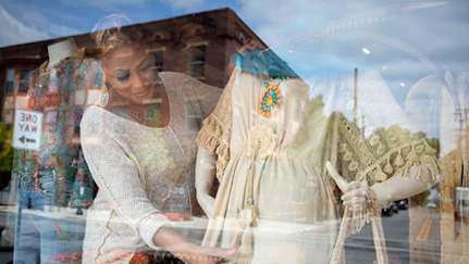 woman in a store window adjusting a dress on a mannequin