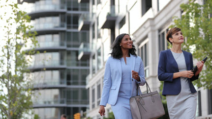 two business women walking down the sidewalk