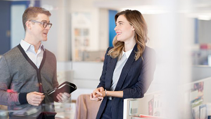 woman and man standing and talking in office
