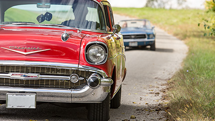Red classic car being followed by a dark blue classic car driving down a road