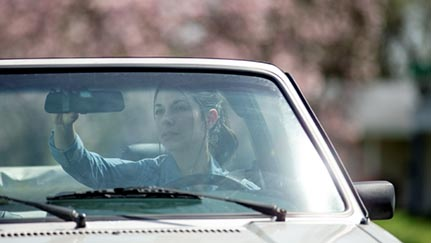 young woman checking rear view mirror in convertible
