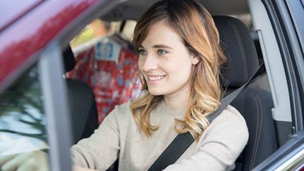 young woman driving maroon car
