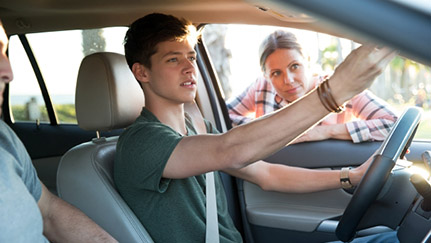 Teenage boy adjusting rearview mirror while mom leans on driver side door