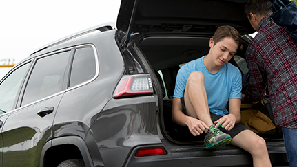 teen sitting in the trunk of a vehicle tying his shoe