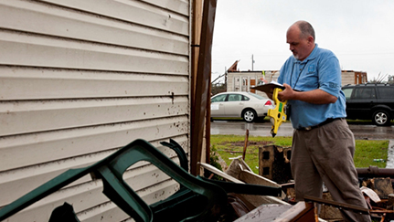 man surveying weather damage outside of a home