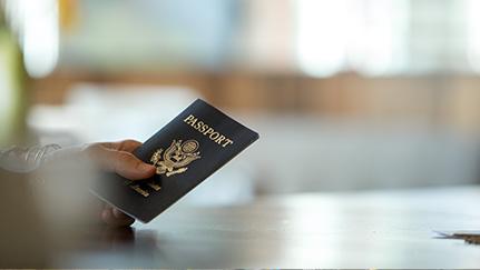 Un viajero sosteniendo su pasaporte sobre el mostrador