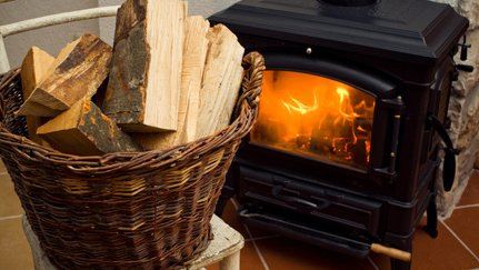 A basket of wood in front of a lit wood stove