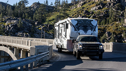 pickup truck towing rv trailer down a curved road