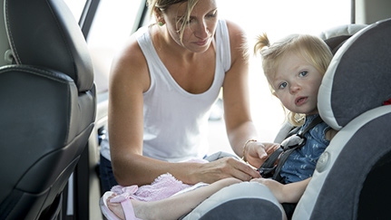 woman fastening child in car seat