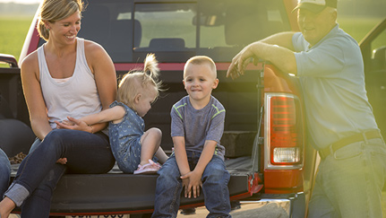 family sitting on the back of a pickup truck