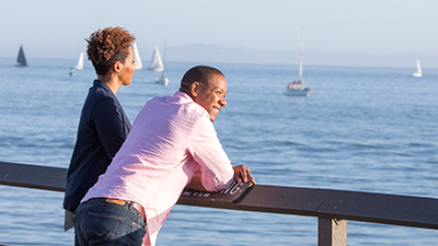 couple gazing at sailboats on the water