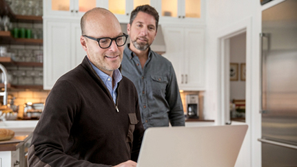 Two men looking at laptop in kitchen