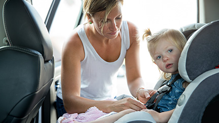 Mother putting a toddler into a car seat in a family car