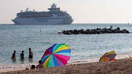 people on a beach with a cruise ship in the background