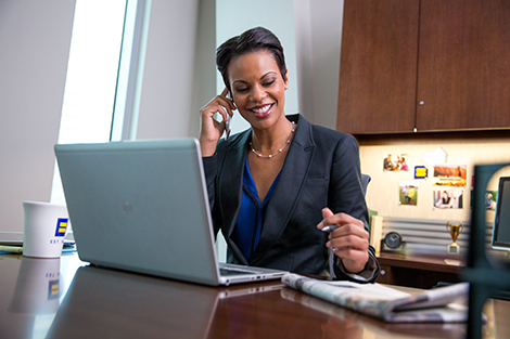 Woman in office talking on phone with laptop