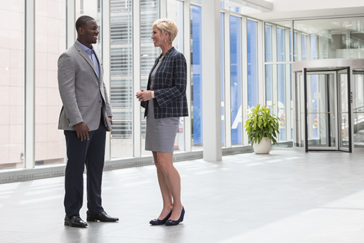 Man and woman talking in office building hall