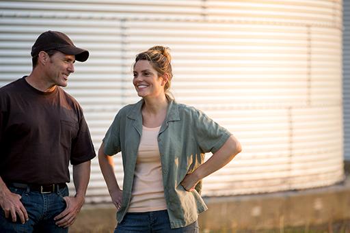 granjeros sonriendo cerca de un silo