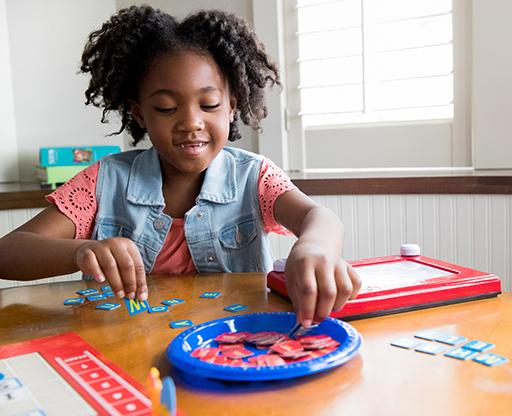 niña jugando un juego con letras sobre la mesa