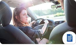 Mujer joven que conduce con un seguro de auto asequible