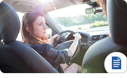 Young woman driving with affordable car insurance
