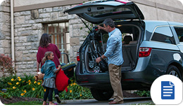 Family unpacking the trunk of a minivan or SUV