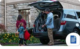 Familia desempacando el maletero de una miniván o SUV