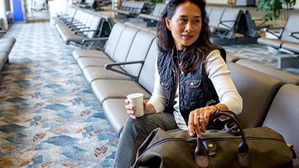 Mujer con una visa sentada en un aeropuerto