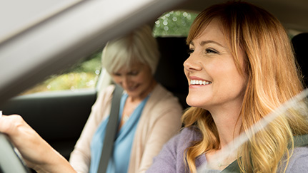 Young woman driving car with older woman