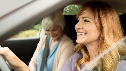 Mujer joven conduciendo con una mujer mayor