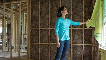 Mujer mirando las ampliaciones de su hogar en construcción