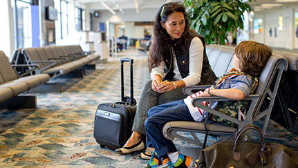 Woman and child with carry-on luggage sitting in an airport