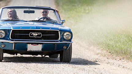 Blue classic car driving on a dirt road