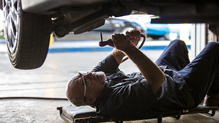 mecánico revisando la parte de abajo de un auto defectuoso