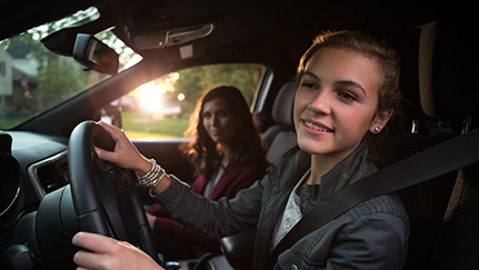 Teen with a learner's permit driving with her mother in the passenger seat.