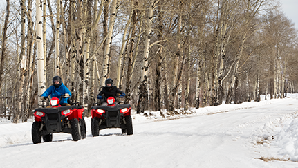 People with helmet riding four-wheeler in snow