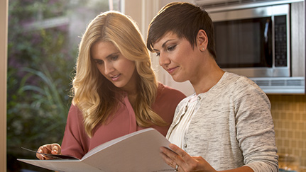 Two women looking through home equity materials in a white folder