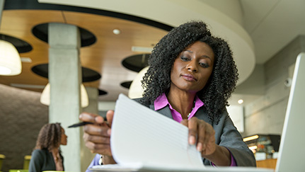 Woman looking over papers, in front of a laptop