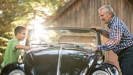 Hombre mayor y niño limpiando un auto clásico negro