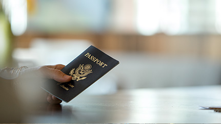 Traveler holding their passport over a counter