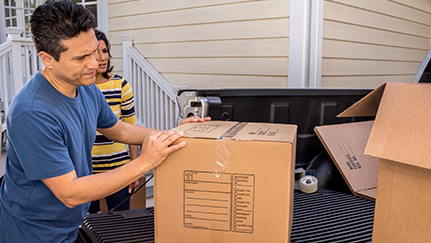 Man and woman unloading boxes from truck bed