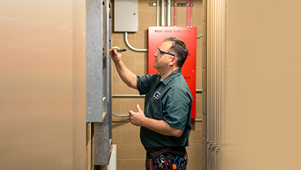 Electrician looking at circuit breaker panel