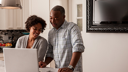 Couple at home on their computer looking at home price estimate tools