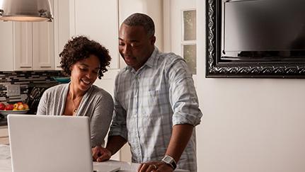 Una pareja en su casa consultando en la computadora herramientas para el cálculo de precios de casas