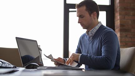 Hombre revisando papeles frente a una laptop